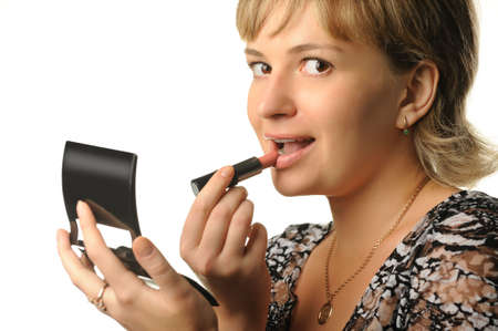 The young girl does a make-up. Paints lips Stock Photo - 5263584