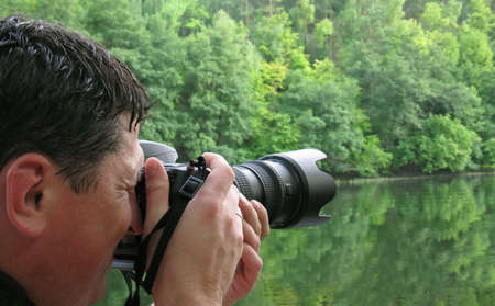 The photographer. The man a photographing landscape - the river with a wood Stock Photo - 5288240