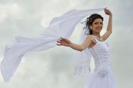 The bride with a fluttering veil. The young girl in a wedding dress. photo