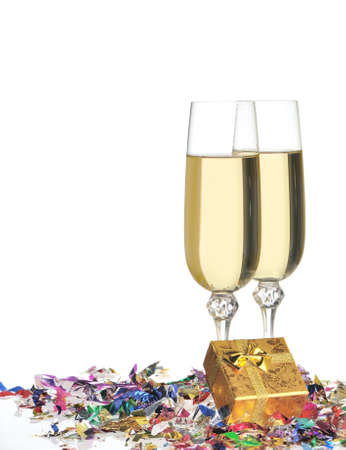 Glasses of a champagne. A celebratory tinsel and a box with a gift photo