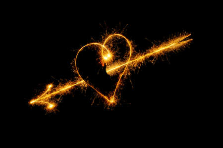 Heart from sparks. It is isolated on a black background photo