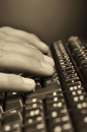 Hands above the keyboard. On a dark background, the black keyboard photo