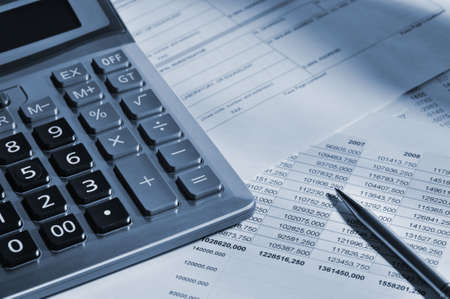 The calculator and the financial report. A workplace of the businessman. High contrast photo