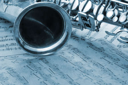 sax: Old saxophone and notes. The Musical instrument laying on notes with classical music of the beginning of 17 centuries