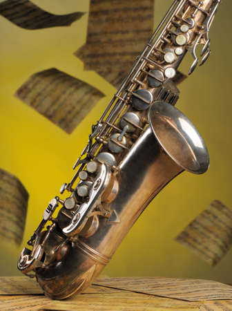 Old saxophone and flying musical notes on a background. The Musical instrument standing on notes with classical music of the beginning of 17 centuries photo