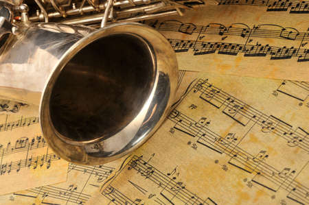 the tenor: Old saxophone and notes. The Musical instrument laying on notes with classical music of the beginning of 17 centuries