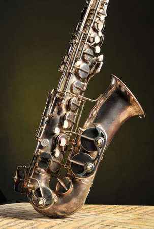 Old saxophone and notes. The Musical instrument standing on notes with classical music of the beginning of 17 centuries photo