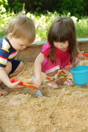 sandbox: The boy and girl playing to a sandbox. Caucasian the child, park of rest Stock Photo
