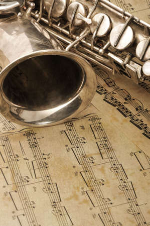 Old saxophone and notes. The Musical instrument laying on notes with classical music of the beginning of 17 centuries photo
