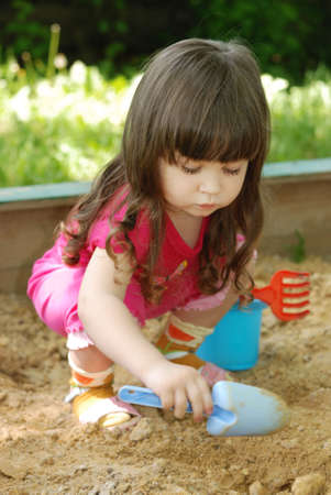 sandbox: The girl playing to a sandbox. Caucasian the child, park of rest Stock Photo