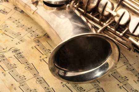 soprano: Old saxophone and notes. The Musical instrument laying on notes with classical music of the beginning of 17 centuries