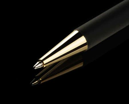 ballpoints: Black pen on a black background. Yellow metal