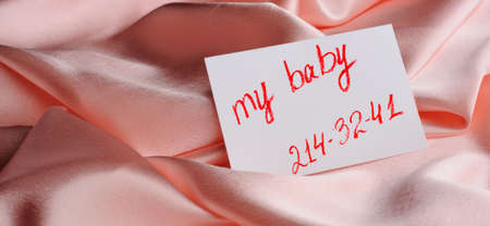 phone number: Note on beige silk. With an inscription  My baby  and an invented phone number. Drawn by lipstick