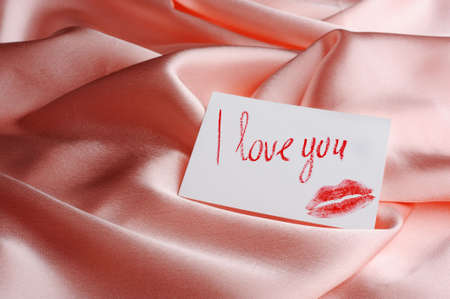 Note on beige silk. With an inscription  I love you   and a print of lips. Drawn by lipstick photo
