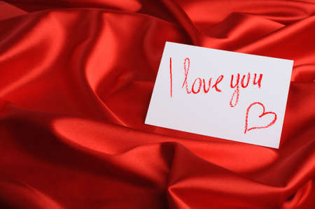 Note on red silk. With an inscription  I love you  and heart. Drawn by lipstick photo