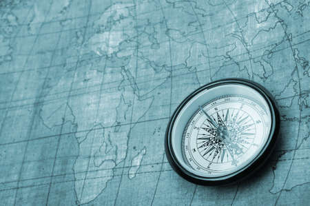 Compass on old map. Blue tone background photo