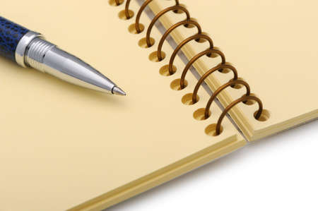 Pen and a notebook on a spiral with a yellow paper. Photo closeup photo