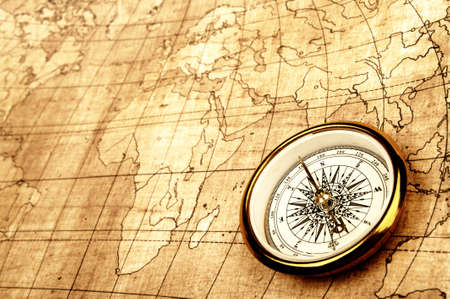 Compass on old map. Gold warm color tone photo