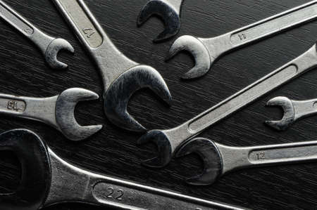 Wrenches. Wrenches on a black wooden surface photo
