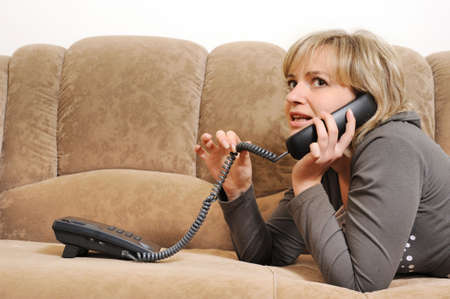 The woman speaking by phone on a sofa.House conditions Stock Photo - 6474816