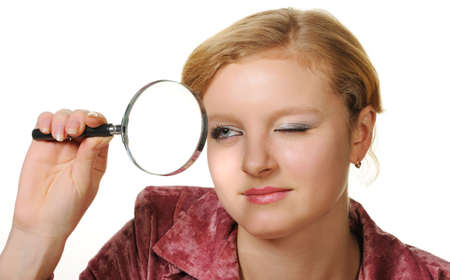 The girl with a magnifier. It is isolated on a white background photo