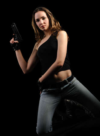 The woman with a pistol. It is isolated on a black background Stock Photo - 6591359