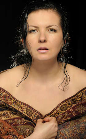 Portrait of the Russian attractive woman with a shawl. A black background photo