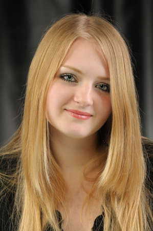 Portrait of the pretty young girl of the blonde. On a black background photo