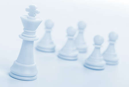 Chess figure - king. Concept of the leader. Pawns on blur a background photo