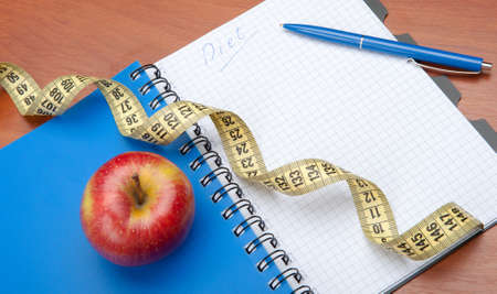 Planning of a diet. A notebook c an inscription - the Diet, a measuring tape, an apple and pen photo