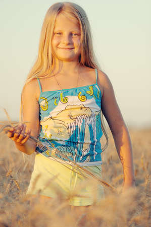 The girl in filed wheats. Warm light sunset Stock Photo - 7386571