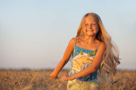 The girl in filed wheats. Warm light sunset Stock Photo - 7386569