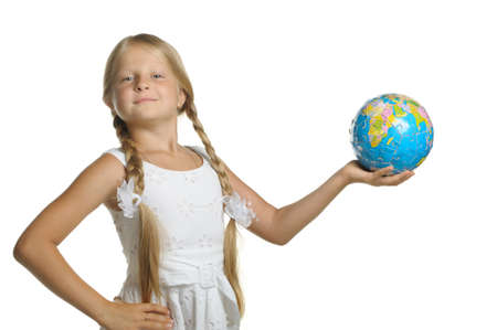 The girl holds the globe collected from puzzle in hands. It is isolated on a white background photo