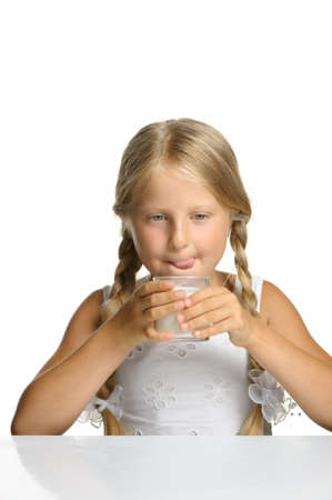 The pretty girl with a glass of milk. It is isolated on a white background photo