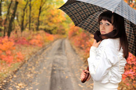 The girl in an autumn wood with a umbrella. The European appearance photo