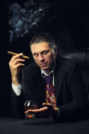 El hombre con un cigarro y un vaso de coñac. Un fondo oscuro