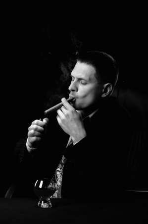 The man with a cigar and a glass of cognac. Monochrome tone. A dark background photo