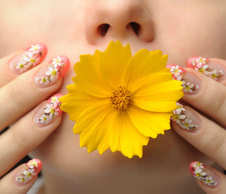 Female face close up c flower in a mouth and nail art. Figure of camomiles on nails photo