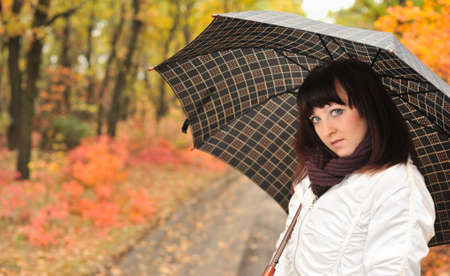 The girl in an autumn wood with a umbrella. The European appearance Stock Photo - 7455025