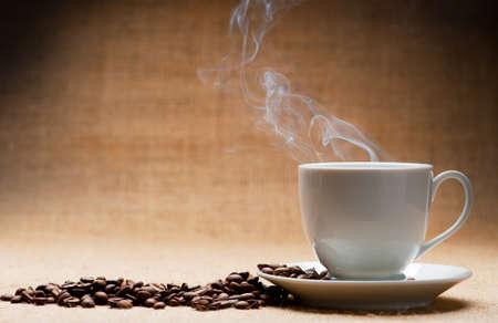 granos de cafe: Taza de caf� caliente sobre el ferry y granos de caf� sobre un fondo de grunge. Viejo tono  Foto de archivo