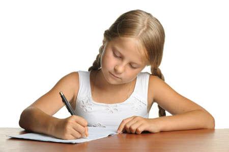 ni�os escribiendo: La chica se escribe en libros de la escritura. La decisi�n de lecciones. Se encuentra aislada sobre un fondo blanco