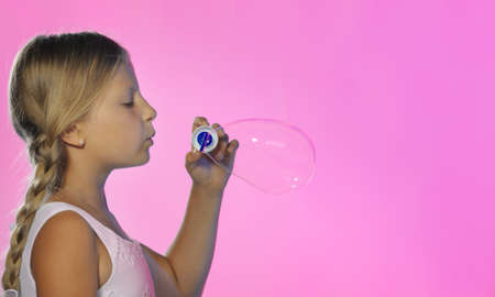 The pretty girl with soap bubbles. A red background photo