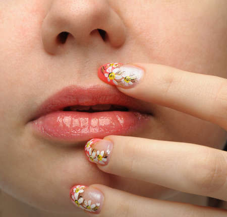 Female face close up and nail art. Figure of camomiles on nails photo