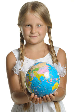 The girl holds the globe collected from puzzle in hands. Selective focus. It is isolated on a white background photo