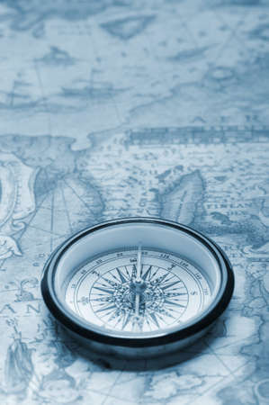 Old compass on ancient map. Blue toned image photo