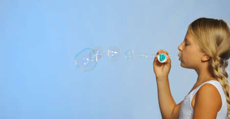 The pretty girl with soap bubbles. A  blue background photo