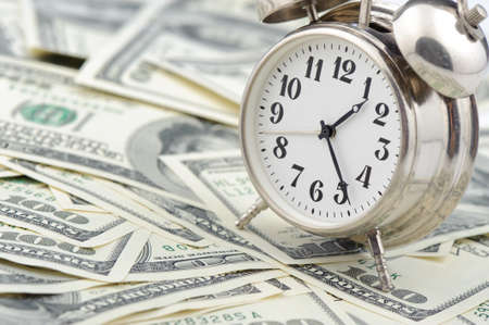 Time - money. Business concept. Analog hours on a heap of paper dollars Stock Photo - 7881208