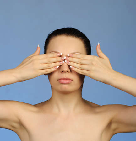 closes eyes: I see nothing. The woman closes eyes hands. A blue background