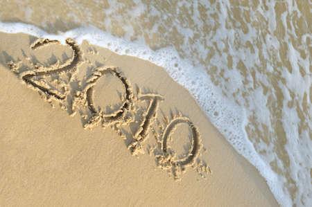 Inscription 2010 on sand. Sea coast with a rolling wave on an inscription photo