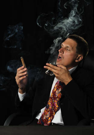The man with a cigar and a glass of cognac. A dark background photo